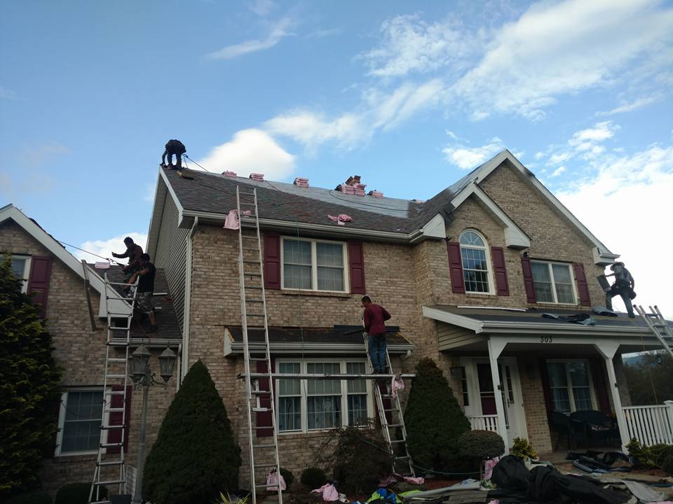 builders working on the roof of a home